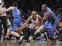 Brooklyn Nets forward Keith Bogans (10) cuts between Orlando Magic guard J.J. Redick (7) and forward Glen Davis (11) to steal the ball in the fourth quarter of their NBA basketball game in New York, January 28, 2013. REUTERS/Ray Stubblebine