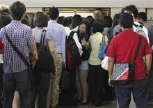 A commuter makes her way past other commuters as she disembarks from a train during the morning peak hour in Singapore January 29, 2013. Singapore's population is projected to reach 6.5 to 6.9 million by 2030, according to a government White Paper released on Tuesday. REUTERS/Edgar Su