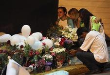 La policía brasileña detuvo el lunes a los dos dueños de una discoteca donde murieron 231 personas y a dos integrantes de una banda cuyos fuegos artificiales habrían incendiado el lugar, a medida que comienza la búsqueda de los responsables de la peor tragedia mundial de ese tipo en una década. En la imagen, la gente llora frente a un jardín de flores colocado en homenaje a las víctimas del incendio en la discoteca Kiss, en la ciudad de Santa María, a 301 km al oeste de la capital del estado Puerto Alegre, el 28 de enero de 2013. REUTERS/Edison Vara