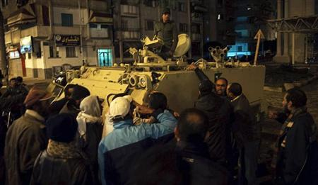 DATE IMPORTED: January 29, 2013 Protesters, who are against Egyptian President Mohamed Mursi, gather near a military tank as they take part in a march during a nighttime curfew in the city of Port Said January 28, 2013. Egyptian protesters defied a nighttime curfew in restive towns along the Suez Canal, attacking police stations and ignoring emergency rule imposed by Islamist President Mursi to end days of clashes that have killed at least 52 people. Picture taken January 28. REUTERS/Stringer (EGYPT - Tags: POLITICS CIVIL UNREST MILITARY)