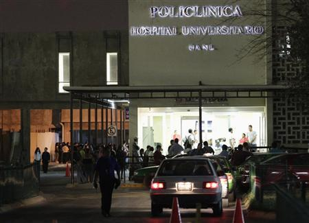 People wait outside a morgue (L), where the dozen bodies found inside a well in northern Mexico were relocated to, at the University Hospital in Monterrey January 28, 2013. REUTERS/Daniel Becerril