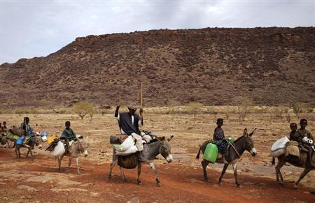 DATE IMPORTED: January 28, 2013 A farmer waves while riding a donkey with his family near Douentza January 28, 2013. REUTERS/Joe Penney (MALI - Tags: CIVIL UNREST POLITICS CONFLICT SOCIETY)