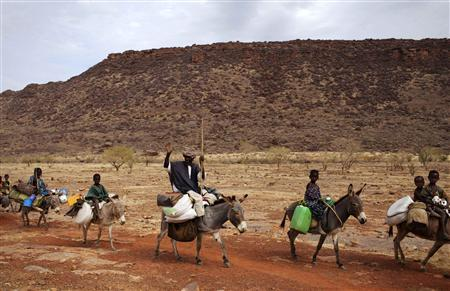 A farmer waves while riding a donkey with his family near Douentza January 28, 2013. REUTERS/Joe Penney