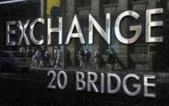 Passanti riflessi nella targa che segnala la Borsa di Sydney. REUTERS/Daniel Munoz