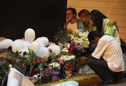 People mourn in front of flowers placed in tribute to the victims of the Kiss nightclub fire, in the southern city of Santa Maria, 187 miles (301 km) west of the state capital Porto Alegre, January 28, 2013. REUTERS/Edison Vara