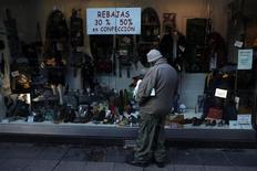 Las ventas minoristas encadenaron en diciembre en España 30 meses de caída en medio de la segunda recesión económica en tres años que ha llevado a una larga debilidad del consumo privado. En la imagen, un hombre mira un escaparte en una zona comercial en Madrid, el 21 de enero de 2013. REUTERS/ Susana Vera