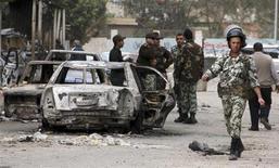 Soldati egiziani vicino a un veicolo dato alle fiamme davanti a una stazione di polizia a Suez. REUTERS/Stringer