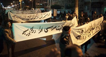Protesters, who are against Egyptian President Mohamed Mursi, carry banners as they march during a nighttime curfew in the city of Port Said January 28, 2013. REUTERS/Stringer