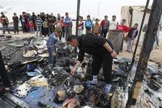 Rifugiati siriani cercano di recuperare qualcosa tra i resti di una tenda bruciata in un campo nella città giordana di Mafraq, vicino alla frontiera. REUTERS/Ali Jarekji