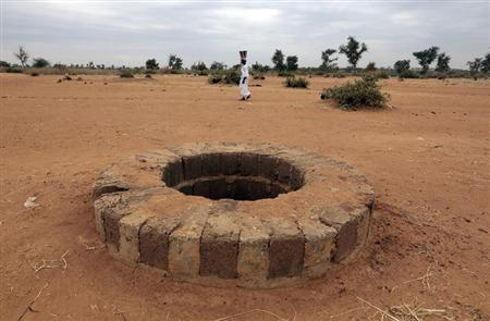 A woman walks past the well where the bodies of suspected Islamist rebels, according to UN director of Human Rights Watch, Philippe Bolopion, had been dumped, in Sevare January 28, 2013. REUTERS/Eric Gaillard (MALI - Tags: CIVIL UNREST CONFLICT TPX IMAGES OF THE DAY
