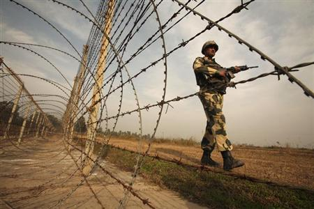 A Border Security Force (BSF) soldier patrols near the fenced border with Pakistan in Suchetgarh, southwest of Jammu January 14, 2013. REUTERS/Mukesh Gupta