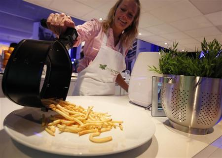 A woman serves french fries prepared in an 'AirFryer', which uses hot air instead of cooking oil, at the Philips stand at the Internationale Funkausstellung (IFA) consumer electronics fair at ''Messe Berlin'' exhibition centre in Berlin, September 3, 2010. REUTERS/Christian Charisius