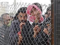 Más de 700.000 sirios han sido registrados como refugiados, o esperan el proceso, en los países vecinos, donde los trabajadores de ayuda tienen dificultades para afrontar el éxodo, dijo el martes la ONU. En la imagen, varios refugiados sirios miran tras la valla en el campo de refugiados Al Zaatri de la localidad jordana de Mafraq el 28 de enero de 2013. REUTERS/Ali Jarekji