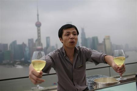 A waiter holds glasses of wine to deliver to guests at a luxury hotel bar near the Bund in Shanghai, September 8, 2012. REUTERS/Aly Song