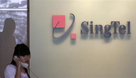 A woman uses a phone at the lobby of a Singtel office in Singapore March 12, 2010. REUTERS/Vivek Prakash