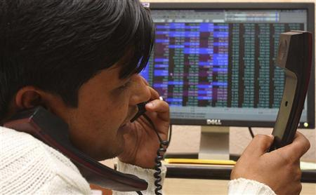 A terminal operator speaks on telephones at a local stock market in Chandigarh December 31, 2009. REUTERS/Ajay Verma/Files