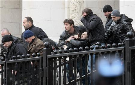Bodyguards carry Zlatomir Ivanov (C) after he was shot in front of the central court building in downtown Sofia January 29, 2013. REUTERS/Gergana Kostadinova/BGNES