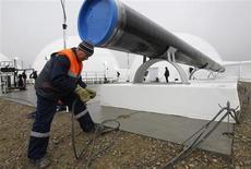 """Рабочий проверяет провода во время церемонии сварки символического шва газопровода Южный Поток в Анапе 7 декабря 2012 года. Газпром раскрыл суммарные расходы на строительство экспортной трансчерноморской магистрали """"Южный поток"""", проектируемой в обход Украины, ценовые споры с которой уже неоднократно останавливали прокачку российского газа в Европу. REUTERS/Sergei Karpukhin"""
