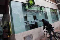La sociedad inmobiliaria del nacionalizado Grupo BFA-Bankia vendió el año pasado 5.600 inmuebles e ingresó 550 millones de euros, un aumento de los ingresos del 18,9 por ciento sobre el año anterior. En la imagen, un ciclista mira por las ventanas de una sucursal de Bankia el 11 de ener ode 2013. REUTERS/Susana Vera