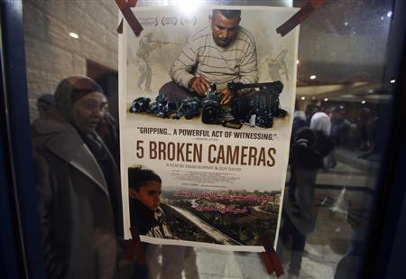 A poster for the Oscar-nominated documentary ''5 Broken Cameras'' is displayed at a theatre in the West Bank city of Ramallah January 28, 2013. REUTERS/Mohamad Torokman