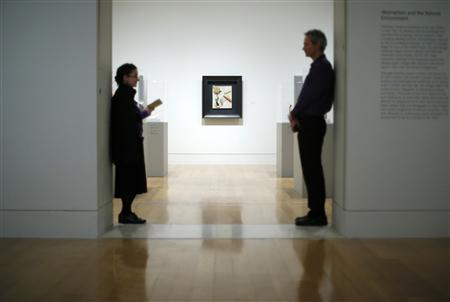 Two gallery security guards pose in front of 'Unitled (heavy relief)' by Kurt Schwitters at the Tate Britain, central London, January 28, 2013. REUTERS/Andrew Winning