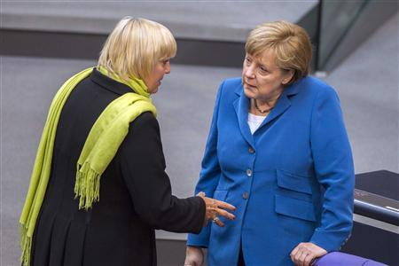 File photo of German Chancellor Angela Merkel (R) talking with the co-leader of the opposition Green Party, Claudia Roth, before a debate at the lower house of parliament, the Bundestag, in Berlin, June 27, 2012. REUTERS/Thomas Peter/Files