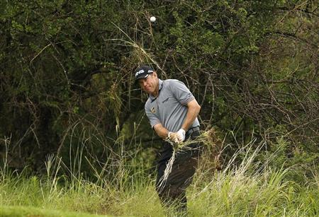Lee Westwood of England plays a shot out of the trees on the 14th hole during the 2012 Nedbank Golf Challenge in Sun City, December 2, 2012. REUTERS/Siphiwe Sibeko