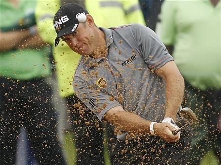 Lee Westwood of England plays a shot out of the bunker on the 14th hole during the final of the 2012 Nedbank Golf Challenge in Sun City, in this file photo talen December 2, 2012. REUTERS/Siphiwe Sibeko