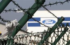 Logotipo da Ford Motor Company é visto por entre arames farpados em unidade da montadora na Bélgica. A Ford previu nesta terça-feira que o lucro operacional de 2013 ficará em linha com os resultados do ano passado, tendo em vista que a maior participação de mercado nos Estados Unidos compensa as crescentes perdas na Europa. 23/10/2012 REUTERS/Francois Lenoir