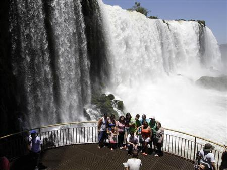 Tourists pose for photos with Iguazu Falls in the background from an observation platform at the Iguazu National Park near southern Brazilian city of Foz do Iguacu January 27, 2013. REUTERS/Jorge Adorno