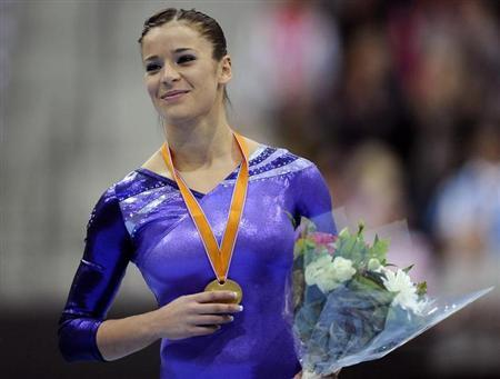 Alicia Sacramone of the U.S. celebrates on the podium with her gold medal after winning the women's vault finals at the Artistic Gymnastics World Championships in Rotterdam October 23, 2010. REUTERS/Dylan Martinez