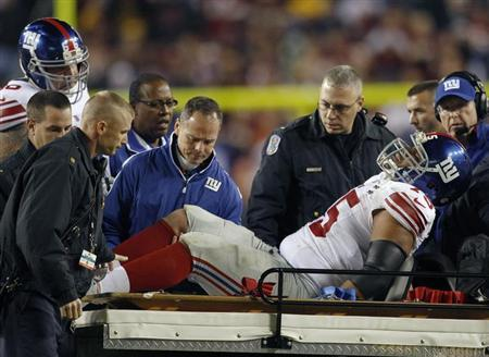 New York Giants tackle Sean Lockler is loaded on to a cart after suffering an injury against the Washington Redskins in the second half of their NFL football game in Landover, Maryland December 3, 2012. REUTERS/Gary Cameron