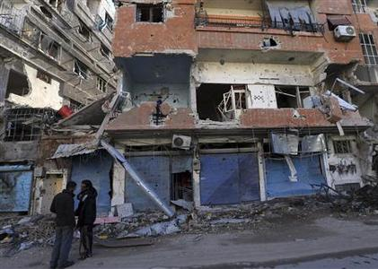 Free Syrian Army fighters stand in front of buildings damaged during fighting in the Haresta neighborhood of Damascus January 29, 2013. REUTERS/Goran Tomasevic