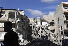 """Un soldado del Ejército de Siria Libre frente a los restos de un edificio derribado tras un ataque de un avión de la Fuerza Aérea en el barrio Haresta de Damasco, ene 29 2013. Al menos 65 personas fueron encontradas ejecutadas y con sus manos atadas el martes en la ciudad de Aleppo, en el norte de Siria, en una nueva """"masacre"""" en el levantamiento de casi dos años contra el presidente Bashar al-Assad, dijeron activistas. REUTERS/Goran Tomasevic"""