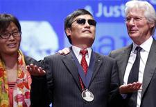 Actor Richard Gere (R) stands with Chinese dissident Chen Guangcheng (C) and his wife Yuan Weijing after Chen received The Tom Lantos Human Rights Prize in the Capitol in Washington January 29, 2013. Gere is a member of the Lantos Foundation advisory board. REUTERS/Kevin Lamarque (UNITED STATES - Tags: POLITICS TPX IMAGES OF THE DAY ENTERTAINMENT)