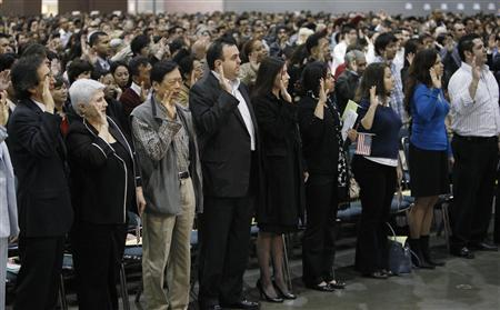 Immigrants, among thousands of others, take the oath of allegiance to the U.S. constitution as they take the final step to becoming a naturalized U.S. citizen during a naturalization ceremony in Los Angeles, March 31, 2010. REUTERS/Danny Moloshok
