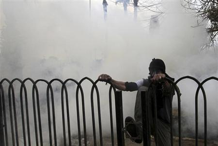 A protester opposing Egyptian President Mohamed Mursi jumps over a gate to run away from riot police during clashes along Qasr Al Nil bridge, which leads to Tahrir Square, in Cairo January 29, 2013. REUTERS/Mohamed Abd El Ghany