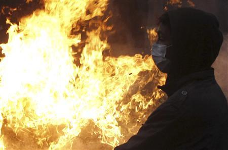 A protester opposing Egyptian President Mohamed Mursi stands in front of fire that they set during clashes with the riot police along Qasr Al Nil bridge, which leads to Tahrir Square, in Cairo January 29, 2013. REUTERS/Mohamed Abd El Ghany