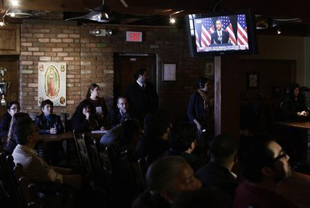 People watch as President Barack Obama speaks about immigration reform on a television monitor at a restaurant in Phoenix, Arizona January 29, 2013. REUTERS/Joshua Lott