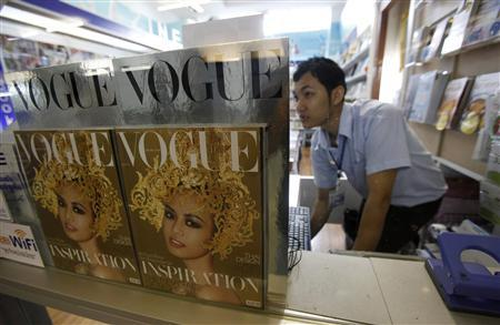 A bookseller works near copies of the Thai edition of Vogue magazine as he waits for customers at a bookstore in Bangkok January 25, 2013. The fashion bible's launch in Thailand on Jan 25 heralded a new era for budding fashionistas and a growing middle class whose tastes are becoming more discerning even as the Thai fashion industry grows more international, highlighted by a twice-yearly fashion week. Picture taken January 25, 2013. REUTERS/Chaiwat Subprasom