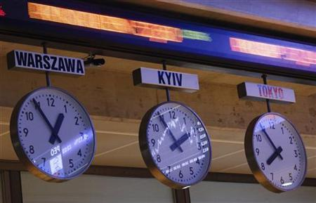 The WIG20 index is seen reflected in clocks showing the time of the different cities in the world at the Warsaw Stock Exchange January 3, 2013. REUTERS-Kacper Pempel