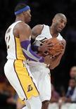 Los Lakers continuaron su buena racha con una victoria por 111-106 frente a los Hornets de Nueva Orleans el martes, en una noche en la que el conjunto local evitó una tardía remontada del rival para registrar su tercera victoria consecutiva. En la imagen, de 27 de enero, Dwight Howard y Kobe Bryant de los Lakers pelean un balón perdido. REUTERS/Alex Gallardo