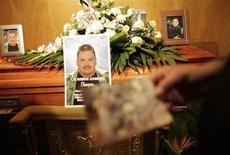 Las autoridades mexicanas concluyeron el martes el rescate de los cuerpos sin vida de 17 integrantes de un grupo musical que fue secuestrado el fin de semana por un grupo armado en el estado de Nuevo León, en el norte del país. En la imagen, el padre de José Antonio Villarreal, un miembro del grupo Kombo Kolombia, sostiene una fotografía de su hijo cerca de su ataúd durante el funeral en Monterrey, el 29 de enero de 2013. REUTERS/Daniel Becerril