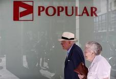 Banco Popular devolverá este miércoles unos 1.300 millones de euros de los préstamos a largo plazo tomados del Banco Central Europeo (BCE) hace algo más de un año y se sumaría a una lista de entidades españolas que pretenden empezar a cancelar una parte de la financiación de forma gradual. En la imagen, una pareja pasa junto a una sucursal de Banco Popular en Sevilla el 3 de octubre de 2012. REUTERS/Marcelo del Pozo