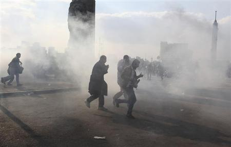 Protesters walk away from tear gas fired by riot police during clashes on Qasr el-Nil bridge, in Cairo January 29, 2013. Egypt's army chief said political unrest was pushing the state to the brink of collapse - a stark warning from the institution that ran the country until last year as Cairo's first freely elected leader struggles to curb bloody street violence. REUTERS/Asmaa Waguih (EGYPT - Tags: POLITICS CIVIL UNREST)