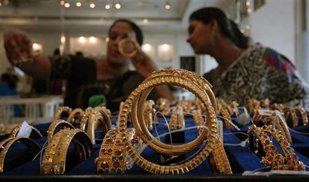 Customers look at gold bangles inside a jewellery shop in Hyderabad September 8, 2009. REUTERS/Krishnendu Halder/Files