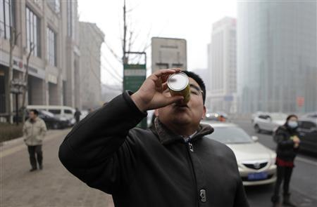 Chinese multimillionaire Chen Guangbiao demonstrates how to use his canned fresh air during an interview with Reuters near a busy street on a hazy day in central Beijing, January 30, 2013. REUTERS/Barry Huang