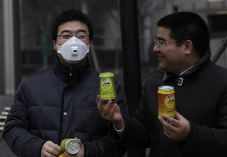 Chinese multimillionaire Chen Guangbiao (R) gives a can of fresh air to a man wearing a mask on a hazy day in central Beijing, January 30, 2013. China's foulest fortnight for air pollution in memory has rekindled a tongue-in-cheek campaign by a Chinese multimillionaire with a streak of showmanship who is raising the alarm by selling canned fresh air. Chen, who made his fortune in the recycling business and is a high-profile philanthropist, on Wednesday handed out soda pop-sized cans of air, purportedly from far-flung and pristine regions of China, from Xinjiang in the far northwest to Taiwan off China's southeast coast. REUTERS/Barry Huang