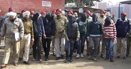 Six men with their faces covered, accused of a gang rape in Punjab are escorted by police to a court at Gurdaspur in the northern Indian state of Punjab January 13, 2013. REUTERS/Stringer