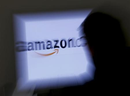 A zoomed illustration image of a man looking at a computer monitor showing the logo of Amazon is seen in Vienna November 26, 2012. To match Special Report TAX-AMAZON REUTERS/Leonhard Foeger (AUSTRIA - Tags: POLITICS BUSINESS
